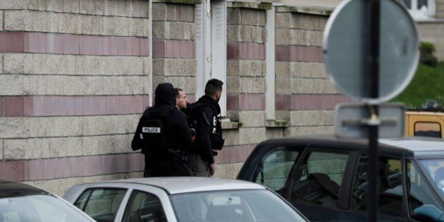Police officers investigate at the house of the suspect of an attack at the Paris Orly's airport, on...