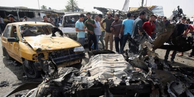 Iraqis check the damage after a suicide bomber detonated an explosives-rigged vehicle in northern Baghdad's...