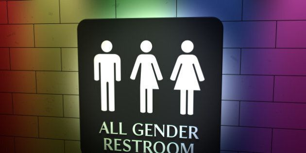 A sign on a wall for All Gender Toilets with symbols for men, trans and women. LGBT issue with pride...