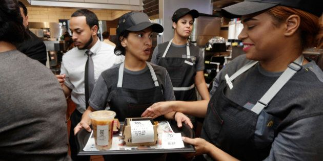 A preparer, center, hands off on order to a table server, right, in the kitchen of a McDonald's restaurant...