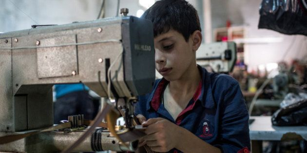 GAZIANTEP, TURKEY - MAY 16: A young Syrian refugee boy makes shoe parts in a Turkish owned factory on...