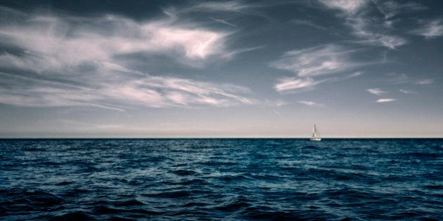 White sailing boat on water with wispy white clouds in