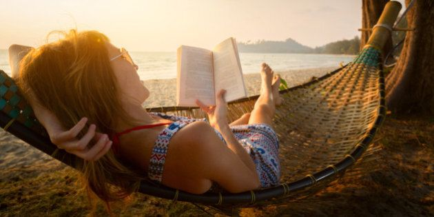 Young lady reading a book in hammock on a beach at