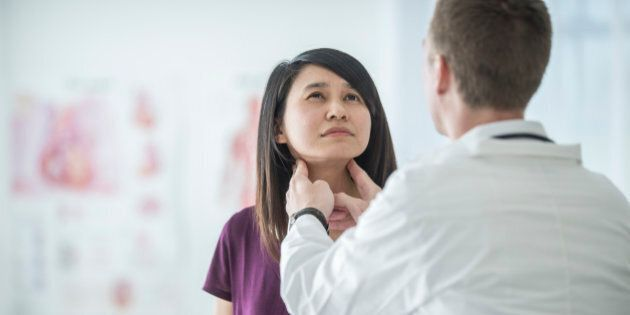 A multi-ethnic group of people are at the doctor's office. A doctor feels a woman's neck for any problems with her lymph nodes or thyroid.