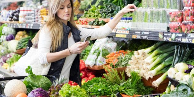 Woman with cart shopping in grocery store in the produce section. Using smart