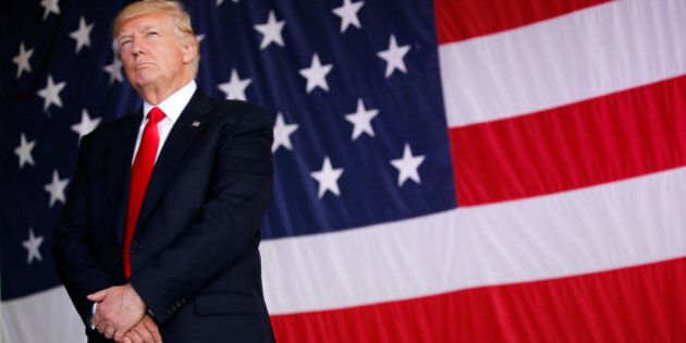 U.S. President Donald Trump stands in front of a U.S. flag while listening to U.S. first lady Melania...