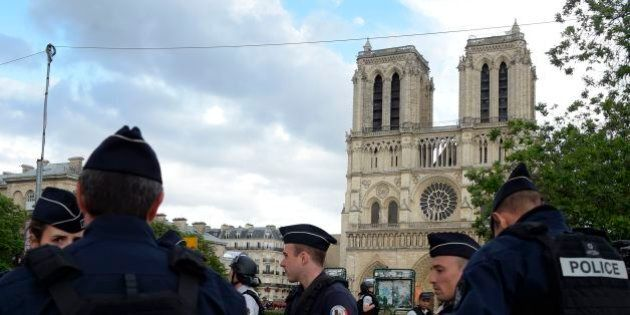 French police officials gather near the site of an attack at the entrance of Notre-Dame cathedral in...