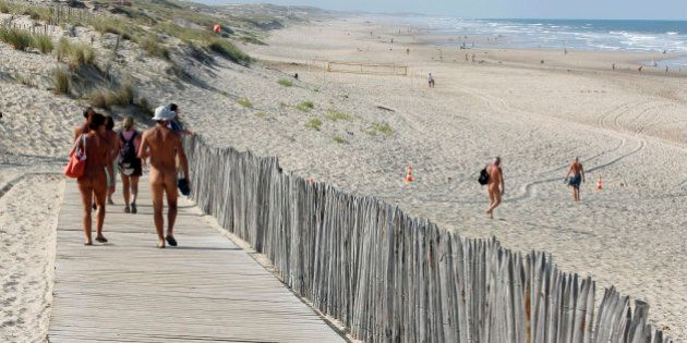 Holiday makers walk on the boardwalk as they make their way to the beach at the Centre Helio-Marin (Center...