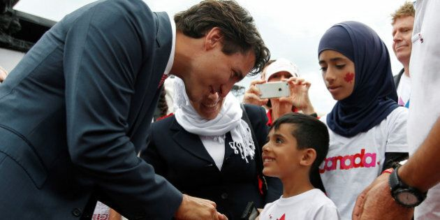 Canada's Prime Minister Justin Trudeau shakes hands with a Syrian refugee during Canada Day celebrations...
