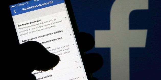 A man reads parameters of security on his phone in front of a displayed Facebook logo in Bordeaux, southwestern...