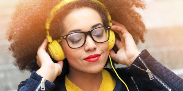 Attractive young woman listening music. Yellow headphones on head, eyeglasses, wear black jacket, yellow...