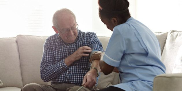 Home carer checking patients blood pressure at home on sofa