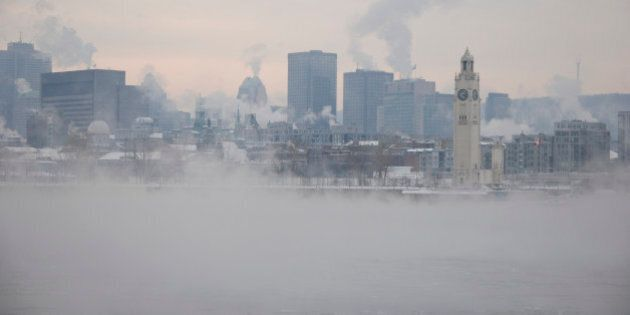 View of Montreal from the other side of St-Lawrence river by a extreme cold winter day.Smog and smoke...