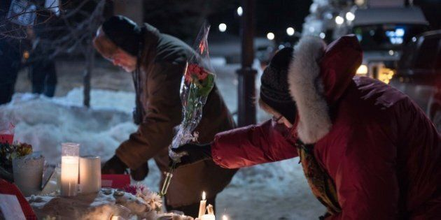 People place candles near a mosque that was the location of a shooting spree in Quebec City, Quebec on...