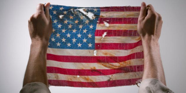 Hands holding torn America flag