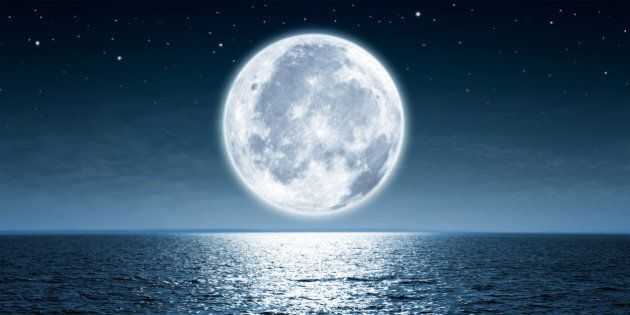 Full moon rising over empty ocean at night with copy