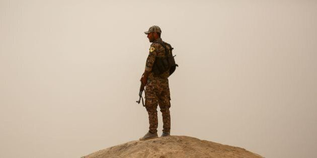 A member of the Kurdish People's Protection Units (YPG) stands guard carrying a Kalashnikov assault rifle...