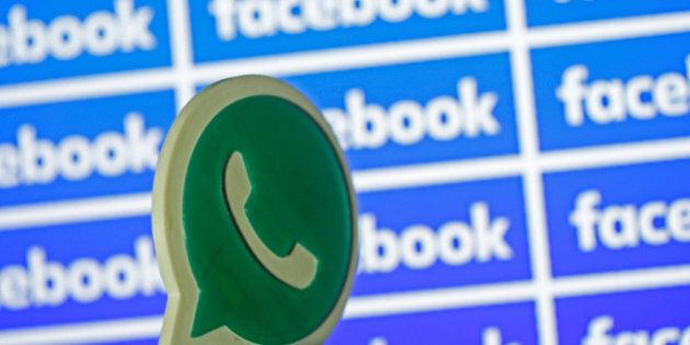 A 3D printed Whatsapp logo is seen in front of a displayed Facebook logo in this illustration taken April...
