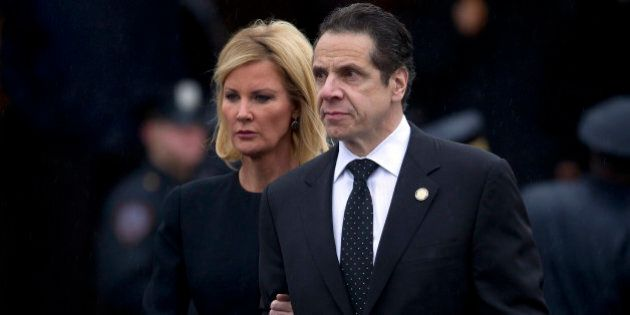 New York Governor Andrew Cuomo and his partner Sandra Lee depart the wake for slain New York Police Department officer Wenjian Liu in the Brooklyn borough of New York January 3, 2015. Liu, 32, and Rafael Ramos, 40, were shot to death on December 20 as they sat in their squad car in Brooklyn. Their killer, Ismaaiyl Brinsley, who killed himself soon after, had said he was seeking to avenge the deaths this summer of two unarmed black men at the hands of white police officers    REUTERS/Carlo Allegri   (UNITED STATES - Tags: SOCIETY CIVIL UNREST CRIME LAW)