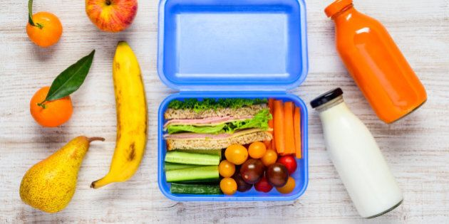 Blue Lunch Box with Sandwiches, Vegetables, Fruits and a Bottle of Milk in Top View