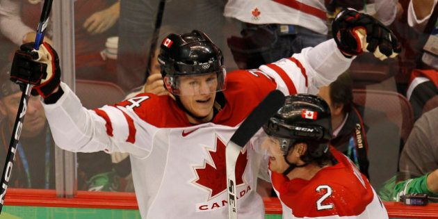 Corey Perry (L) of Canada celebrates his goal against the U.S. in second period of their gold medal hockey...