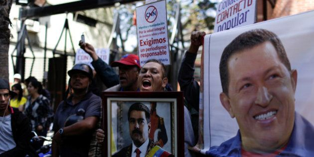 Supporters of Venezuela's President Nicolas Maduro hold images of him and Venezuela's late President...