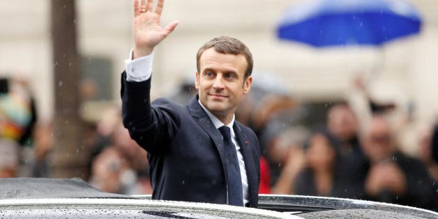 French President Emmanuel Macron waves from his car on the Champs Elysees avenue after the handover ceremony...