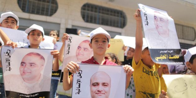 Palestinian demonstrators take part in a protest in solidarity with Mohammad El Halabi, World Vision's manager of operations in Gaza who was accused by Israel of funnelling millions of dollars in aid money to Hamas, organised by foundations and societies benefiting from World Vision in Gaza City August 7, 2016.  (Photo by Momen Faiz/NurPhoto via Getty Images)