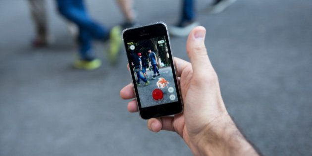 A man plays Nintendo Co.'s Pokemon Go augmented-reality game, developed by Niantic Inc., on their smartphones...