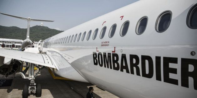 A technician walks under the belly of a Bombardier Inc. CS300 passenger jet at the China International...