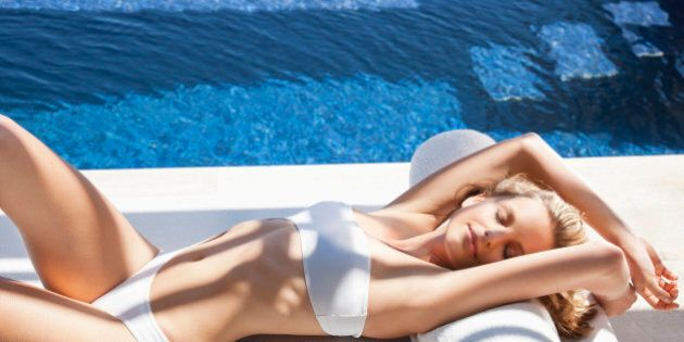 Sexy woman in bikini laying on lounge chair at