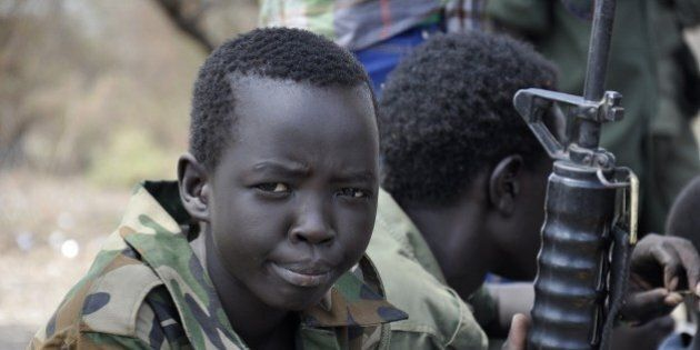 PIBOR, SOUTH SUDAN - FEBRUARY 10 : Young boys, children soldiers sit on February 10, 2015 with their...