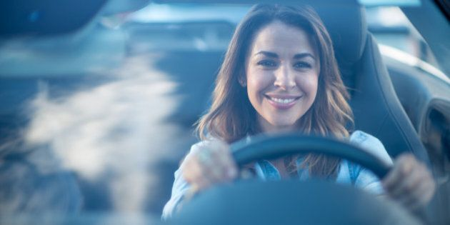 Happy woman driving a car and