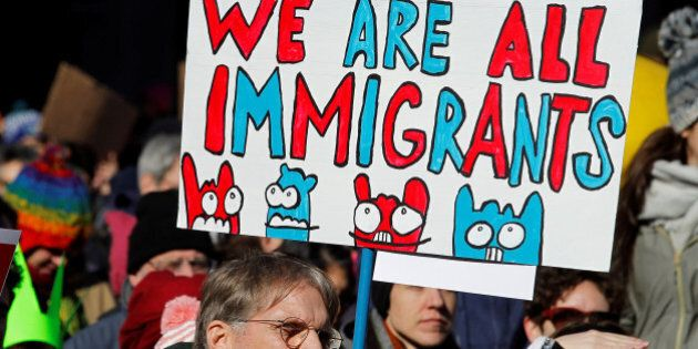 A demonstrator holds a sign to protest against U.S President Donald Trump's executive order banning refugees...