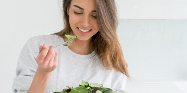 Healthy young woman dieting and eating a salad at home