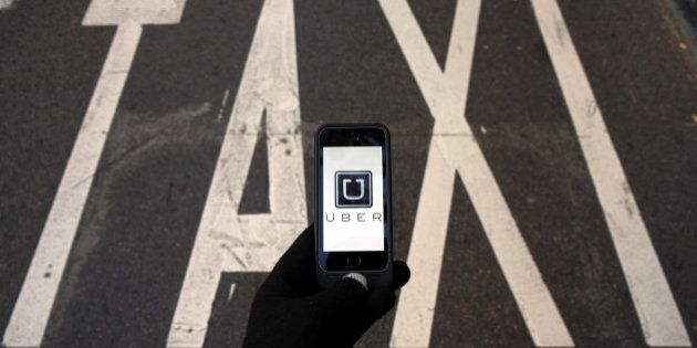 The logo of car-sharing service app Uber on a smartphone over a reserved lane for taxis in a street is...