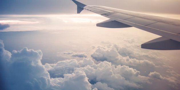 Cropped image of an airplane, only showing the wing while in flight above the