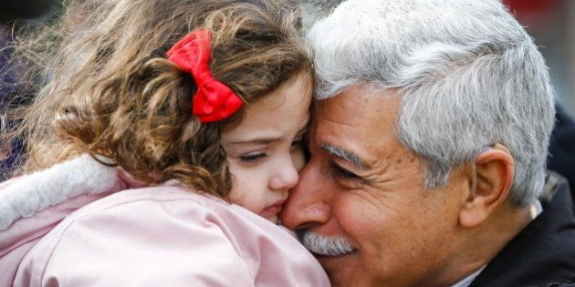 Hagop Manushian, a Syrian refugee who arrived earlier in the morning is reunited with his granddaughter Rita at the Armenian Community Centre of Toronto in Toronto, December 11, 2015. REUTERS/Mark Blinch
