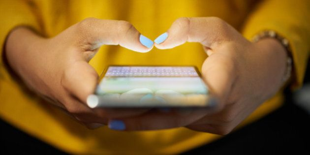 Young woman using cell phone to send text message on social network at night. Closeup of hands with computer...