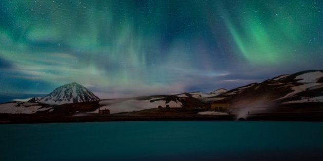 A beautiful aurora dancing over the blue lagoon, Iceland.Geothermal power station and hot water lagoon...