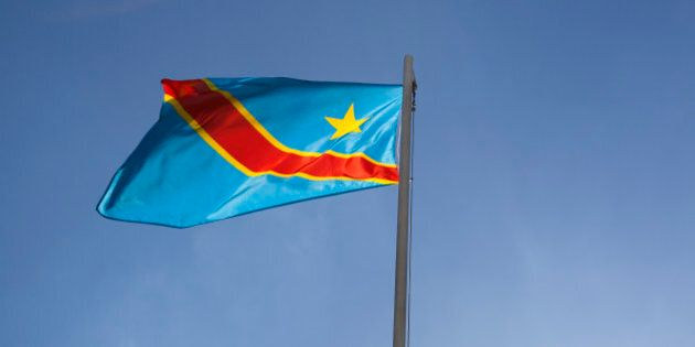 National flag of Congo on a flagpole in front of blue