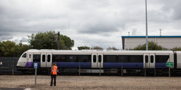A photographer watches an Aventra Class 345 electric multiple-unit test train, manufactured by Bombarider...
