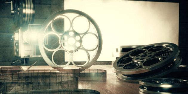 Turning on vintage film camera with old style film cartridges on brown wooden table, retro style photo effect