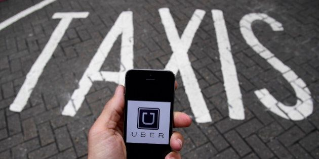A photo illustration shows the Uber app logo displayed on a mobile telephone, as it is held up for a...