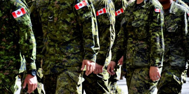 A group of Canadian soldiers wearing green camouflage uniforms march