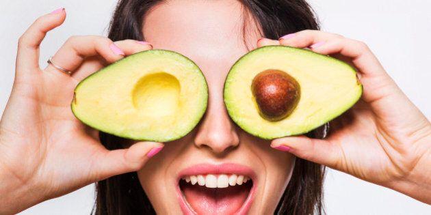 Beauty model holding avocado halves over her