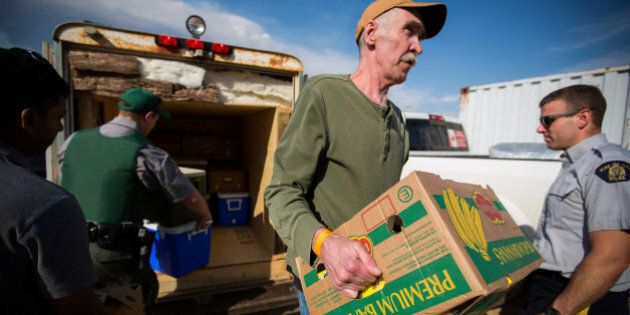Volunteers help carry food into a community centre in Anzac where residents of Fort McMurray have assembled...