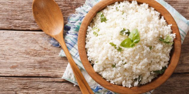 Cauliflower rice with basil close up in a bowl on the table. horizontal top