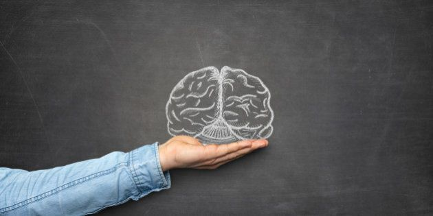 Brain and hand front of blackboard