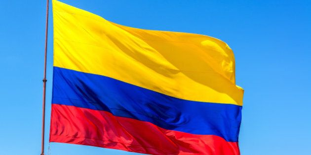 Resplendent Colombian flag waving in the wind set against a beautiful blue